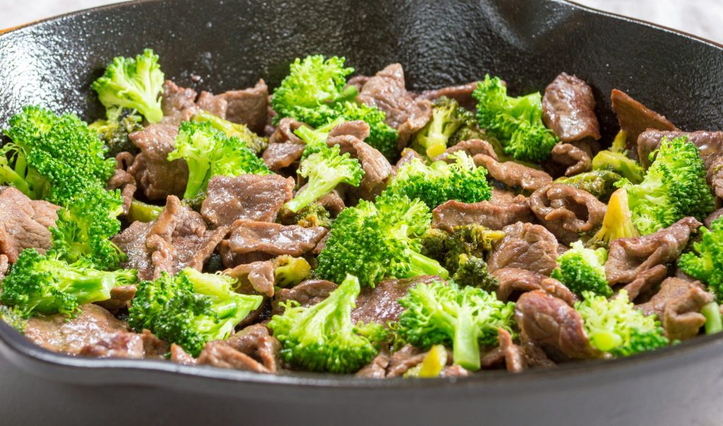 Broccoli and beef cooking in a cast iron skillet.