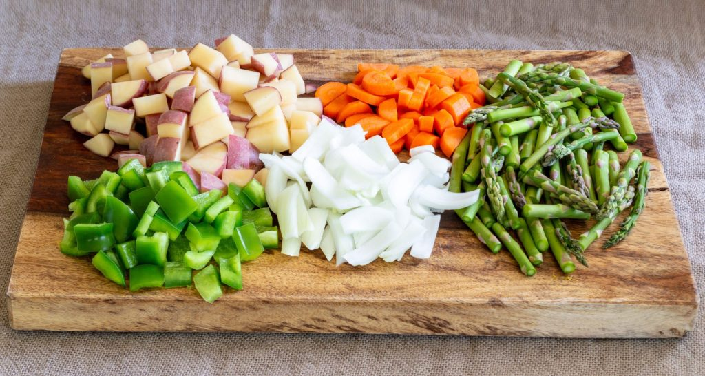 peppers, onion, carrots, onions, and asparagus on a cutting board