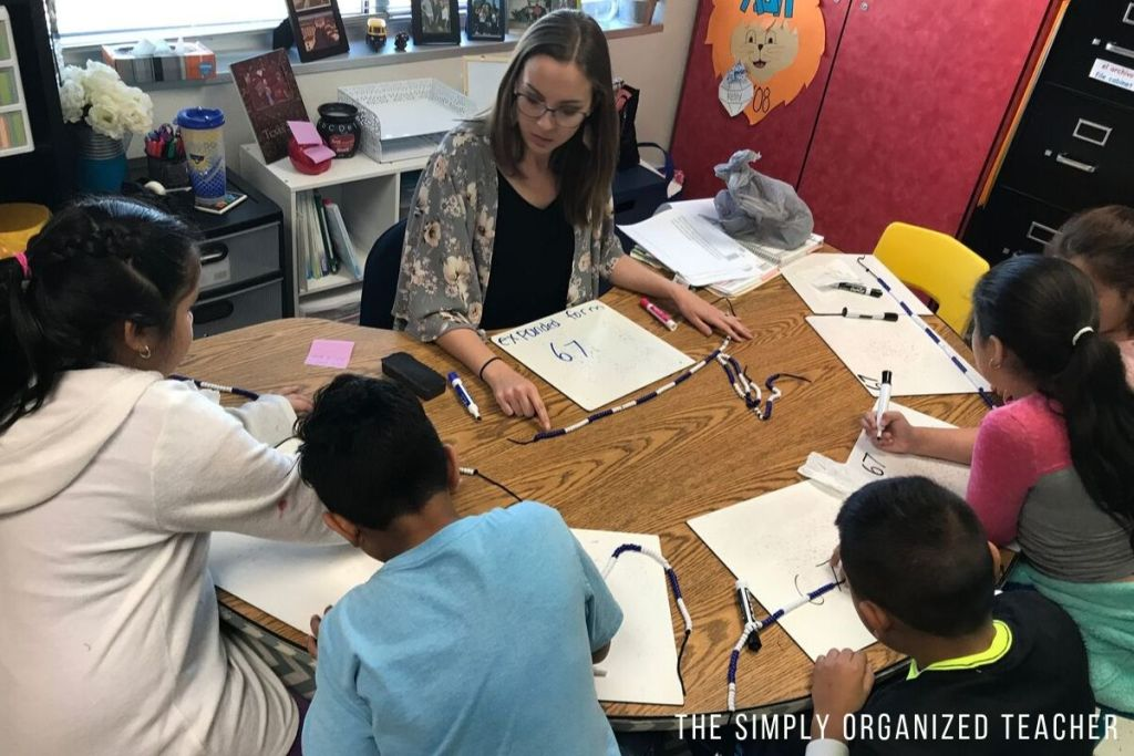 Teacher working with students at a small group teaching table.
