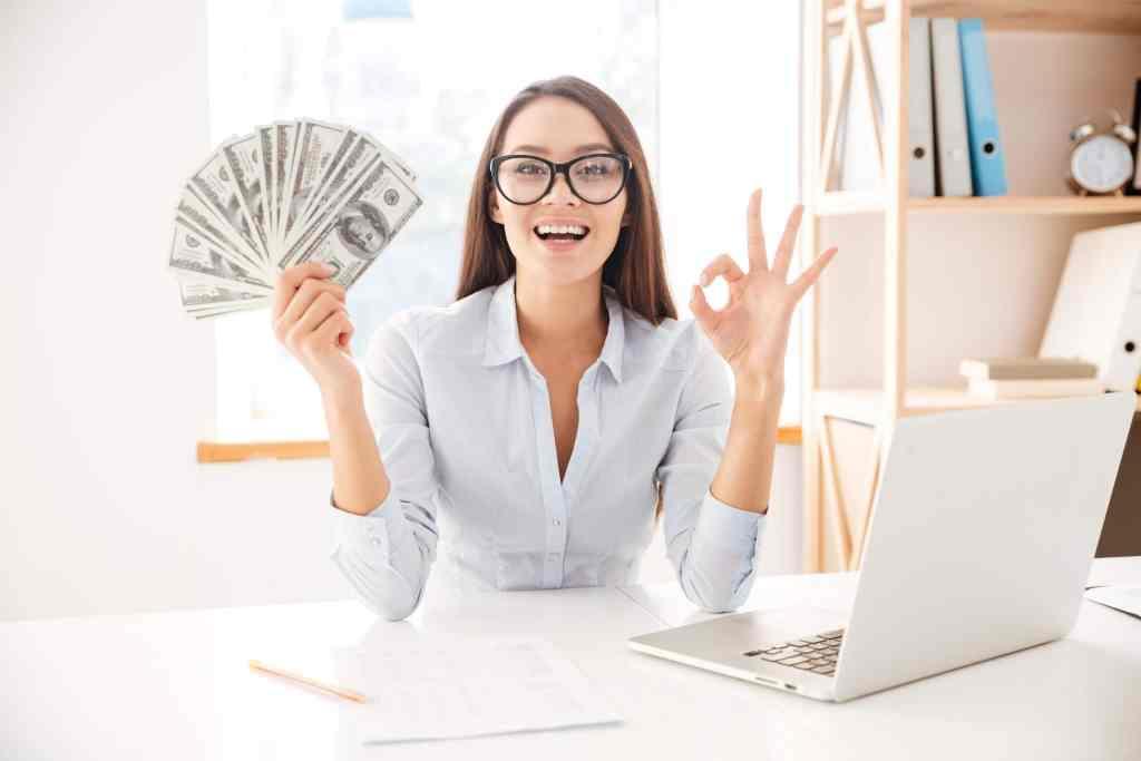 5 Ways to Make Money, woman holding money at desk