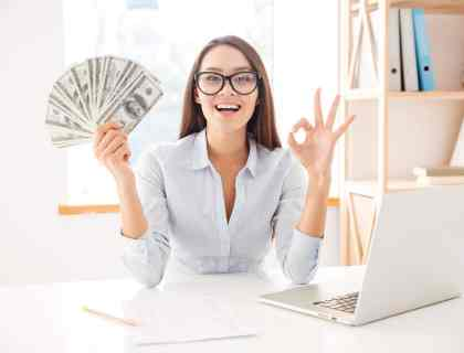 5 Ways to Make Money, woman holding money at desk