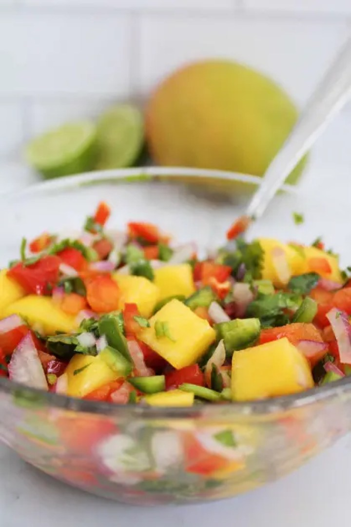Mixing together the ingredients which include mango, habanero pepper, red bell pepper, red onion, cilantro, lime juice, olive oil, salt and pepper.