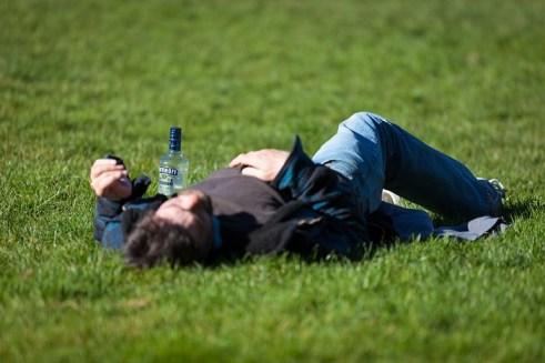 drunk man lying on back smirnoff bottle vodka