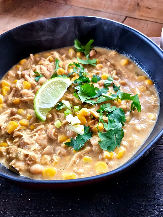 A tantalizing sneak peek at the finished product, a deep bowl of this White Chicken Chili with fresh cilantro and a small slice of lime on top.