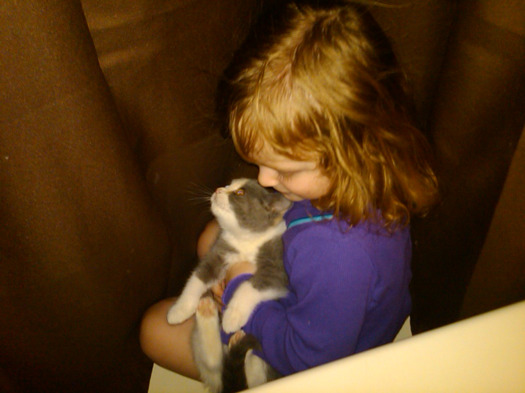 Riley giving Pudding a kiss between the shower curtains.