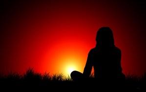 woman watching sunset reflective and thinking