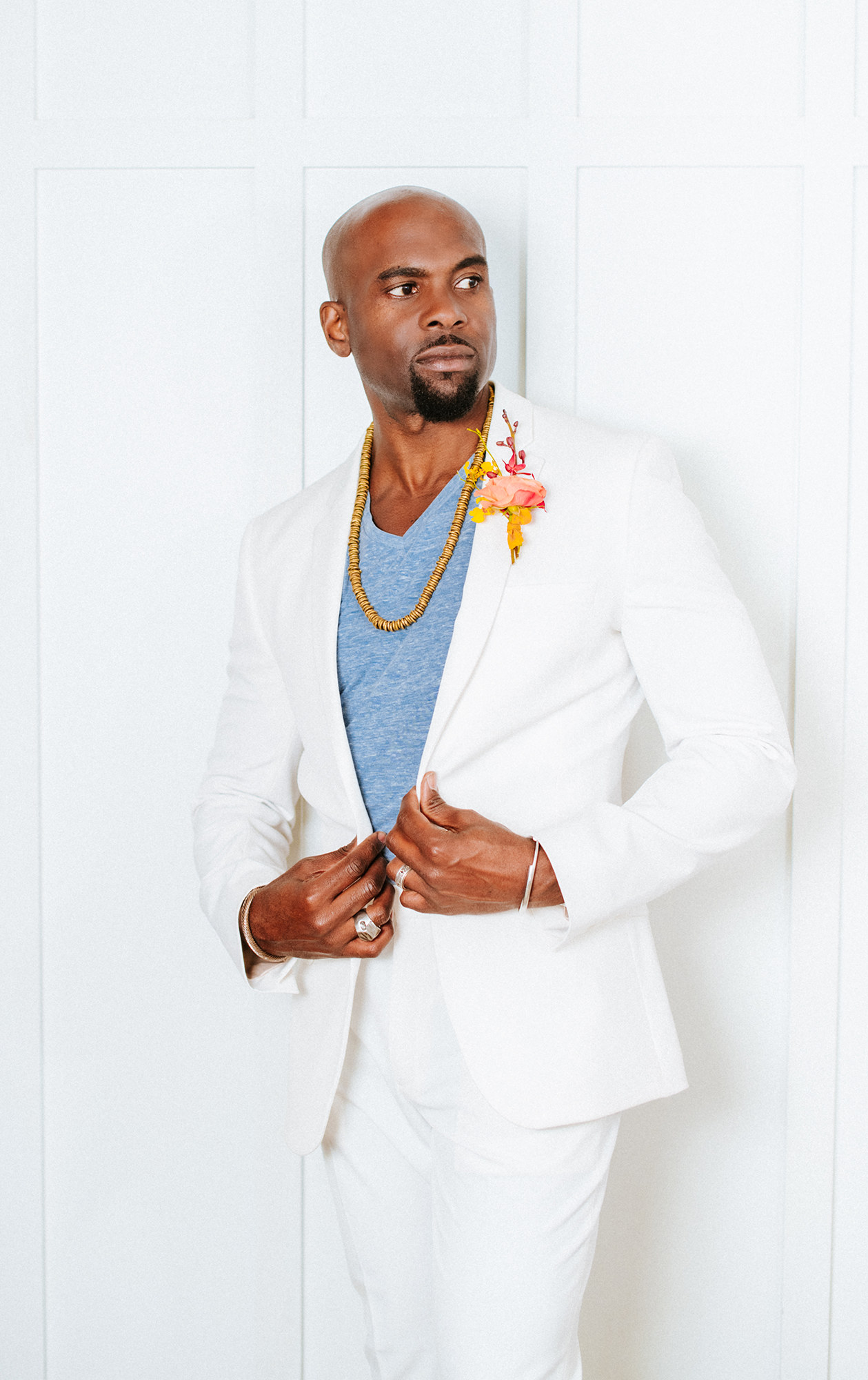 Black groom in white suit with bright boutonniere
