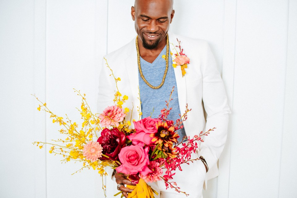 Black groom in white suit with colorful bridal bouquet