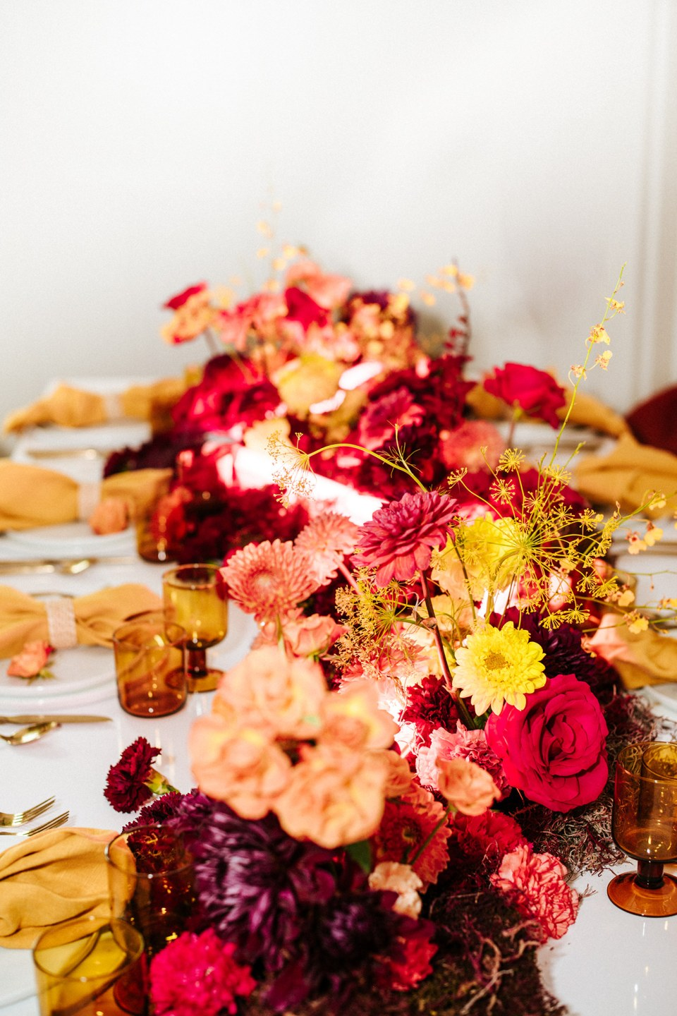 Bright and colorful wedding table decor with floral centerpiece