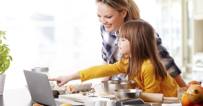 mom blogger with daughter on laptop working in kitchen