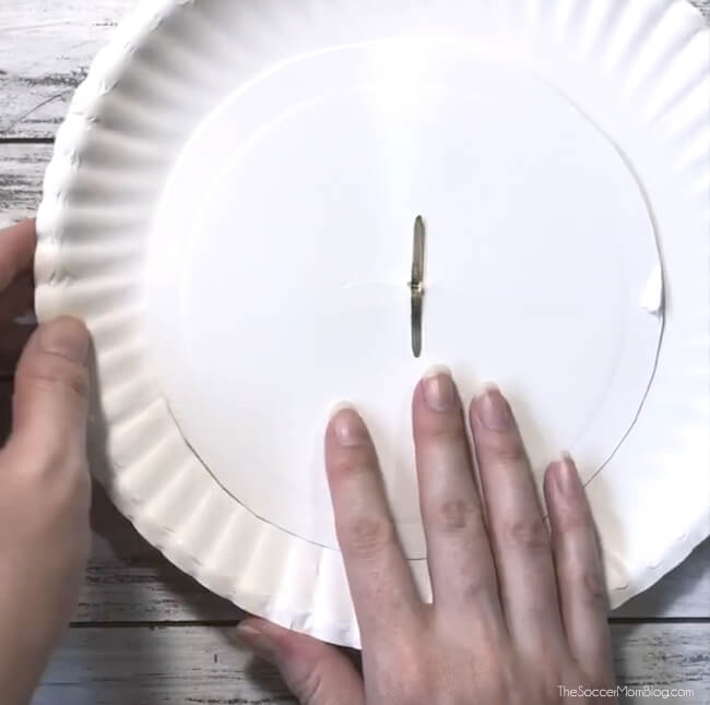 using a brass fastener to attach two paper plates