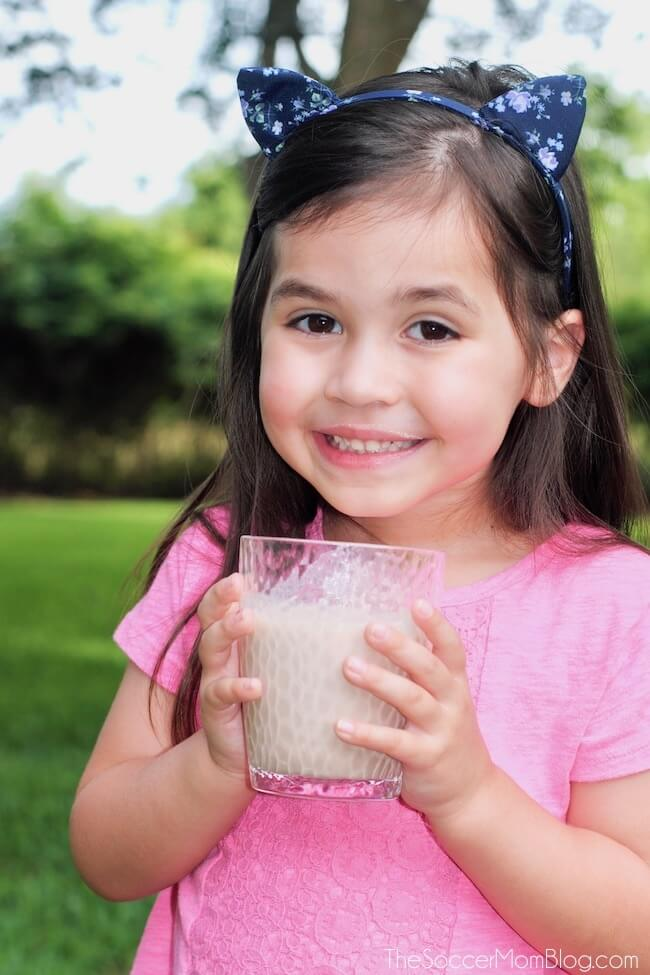little girl smiling and drinking a protein shake