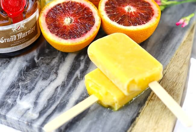 orange popsicles on cutting board