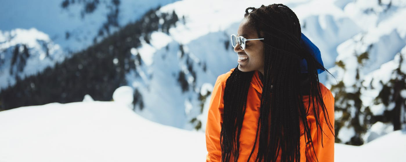 Photo of Judith Kasiama, a woman of colour, with long black hair, wearing sunglasses and an orange jacket, against the backdrop of snow-filled mountains.