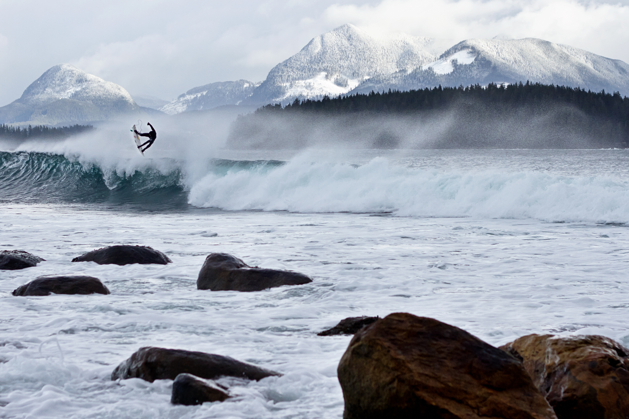 A surfer in the air above a large wave with snow-capped mountains in the background.
