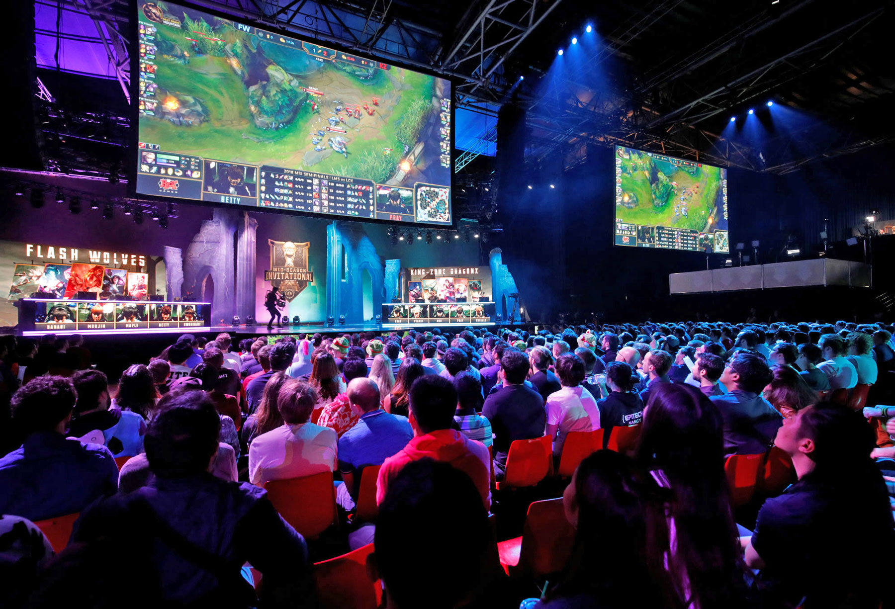 Spectators are seated watching eSports competitors on a stage. A large screen above the competitors displays the game they are playing.