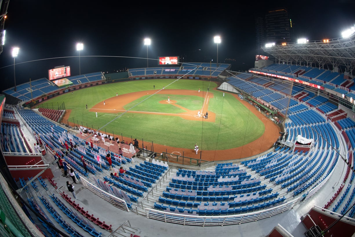A baseball game takes place at night in an empty stadium