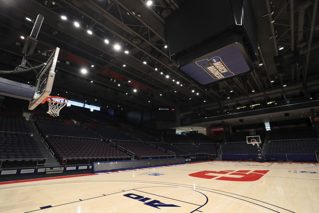 An empty basketball arena with the court lit up