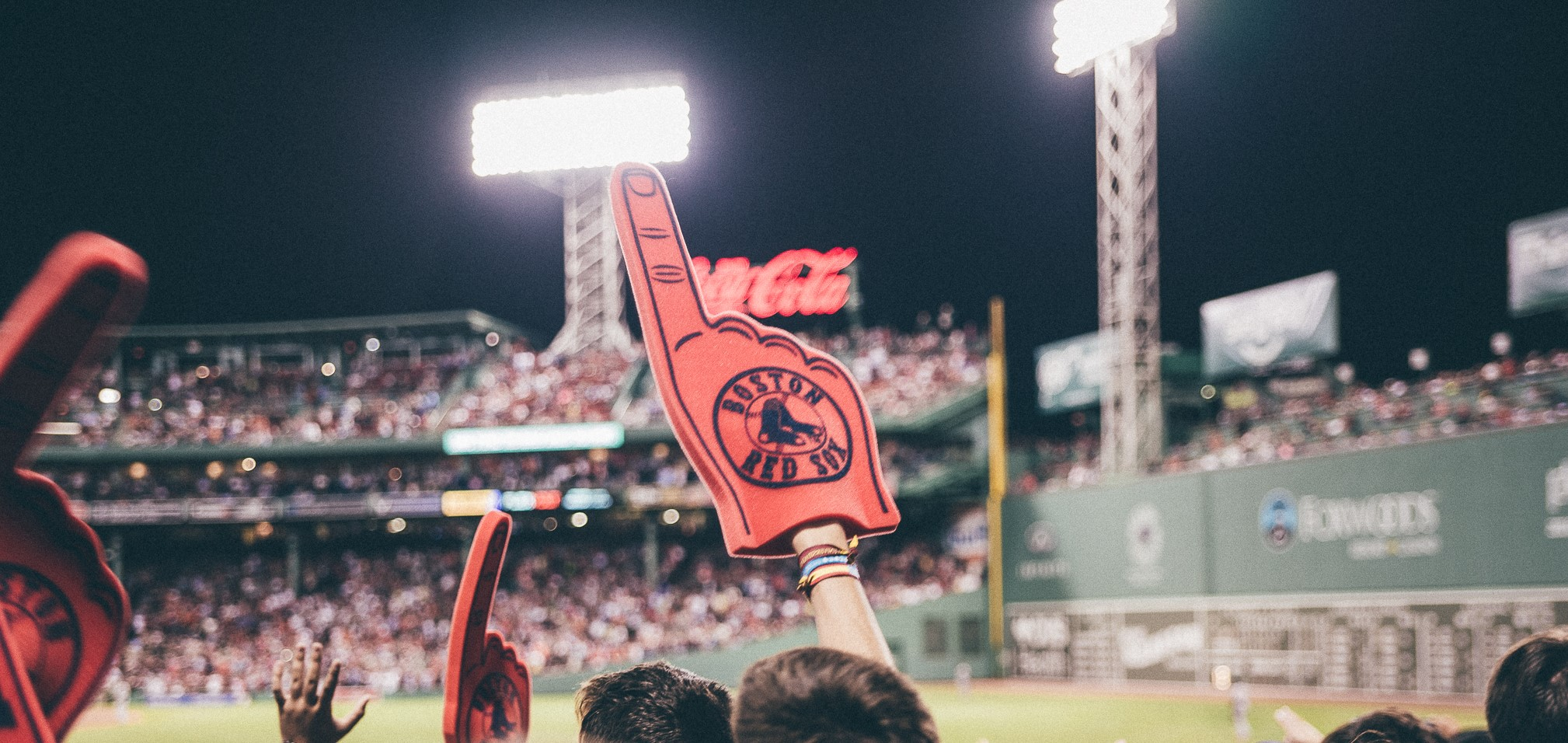 A fan holds up a foam finger while cheering at a Boston Red Sox game at Fenway Park.