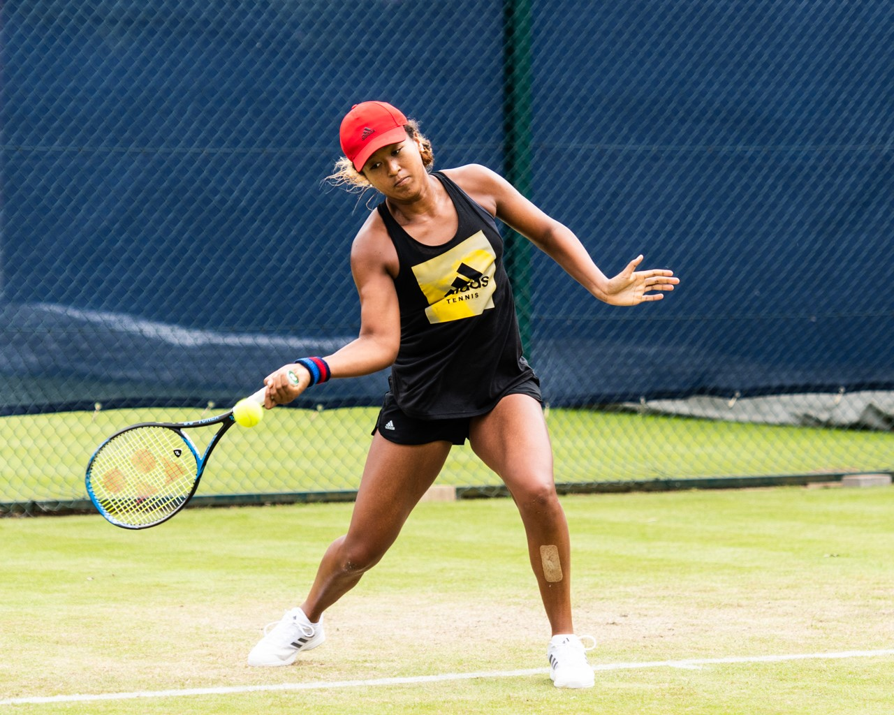 Tennis star Naomi Osaka, wearing a red hat, black tank top, and black shorts, hits a tennis ball with a forehand swing.