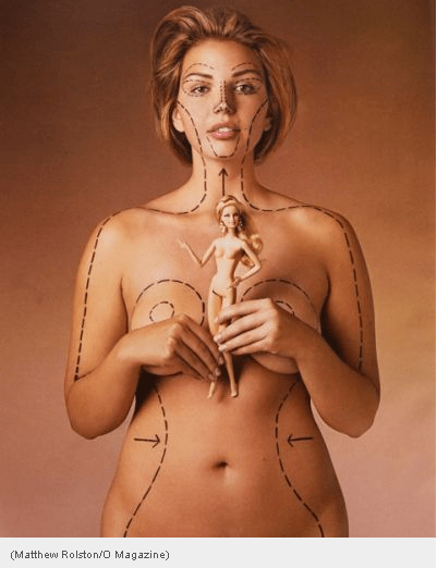 """A white woman's naked body is shown from the hips up, her arms are held in front of her breasts.  She is holding a Barbie doll.  On her body and face are """"surgical lines"""" indicating where she deviates from the Barbie ideal."""