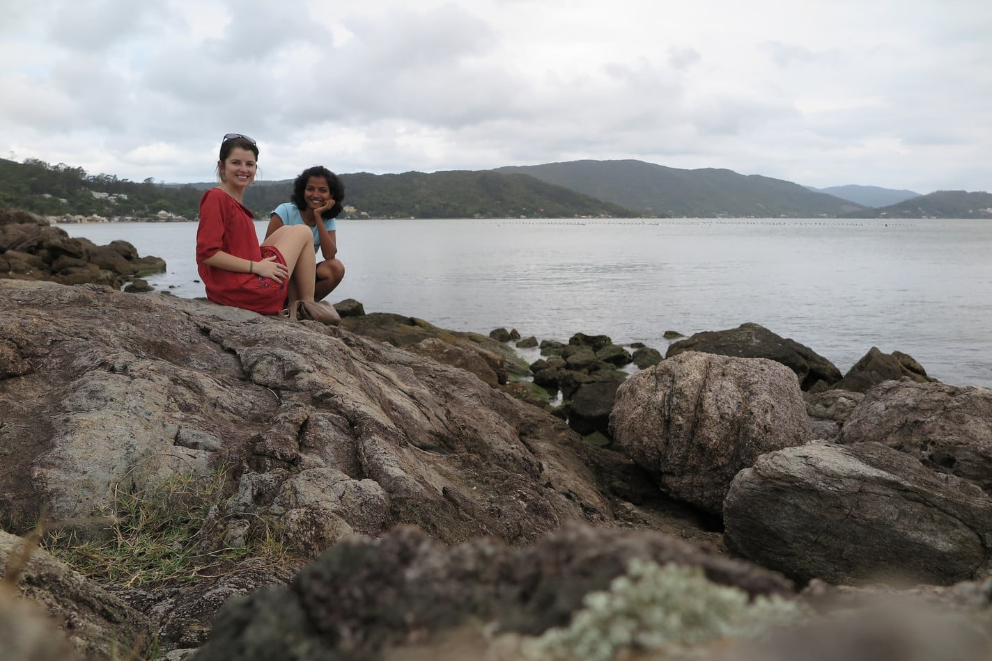 Two women sitting on rocks by the beach