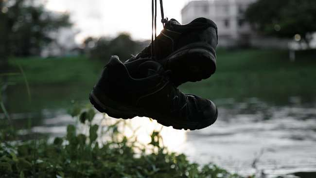 Hiking shoes hanging against the backdrop of a river