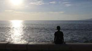 Silhouette of a girl sitting facing the ocean