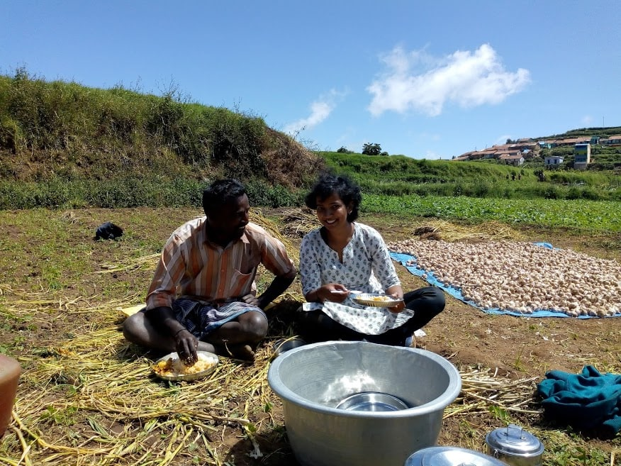 Indian woman eating food with a man in a farm