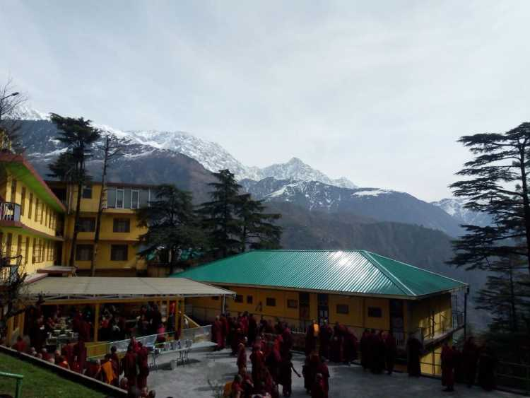 Open area with lot of monks overlooking snow clad mountains