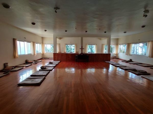 an empty meditation hall with two rows of mats on each side
