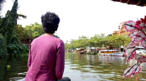 A giel in purple t-shirt sitting on left side on a canoe that is passing by Kerala backwaters