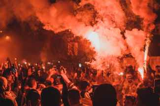 anonymous people standing on street among smoke during protests at night