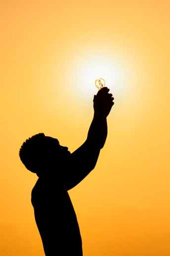 silhouette of man with light bulb at sundown