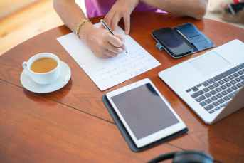 person writing on white paper beside white ceramic mug on brown wooden table