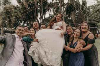 happy ethnic guests carrying bride in white dress in countryside