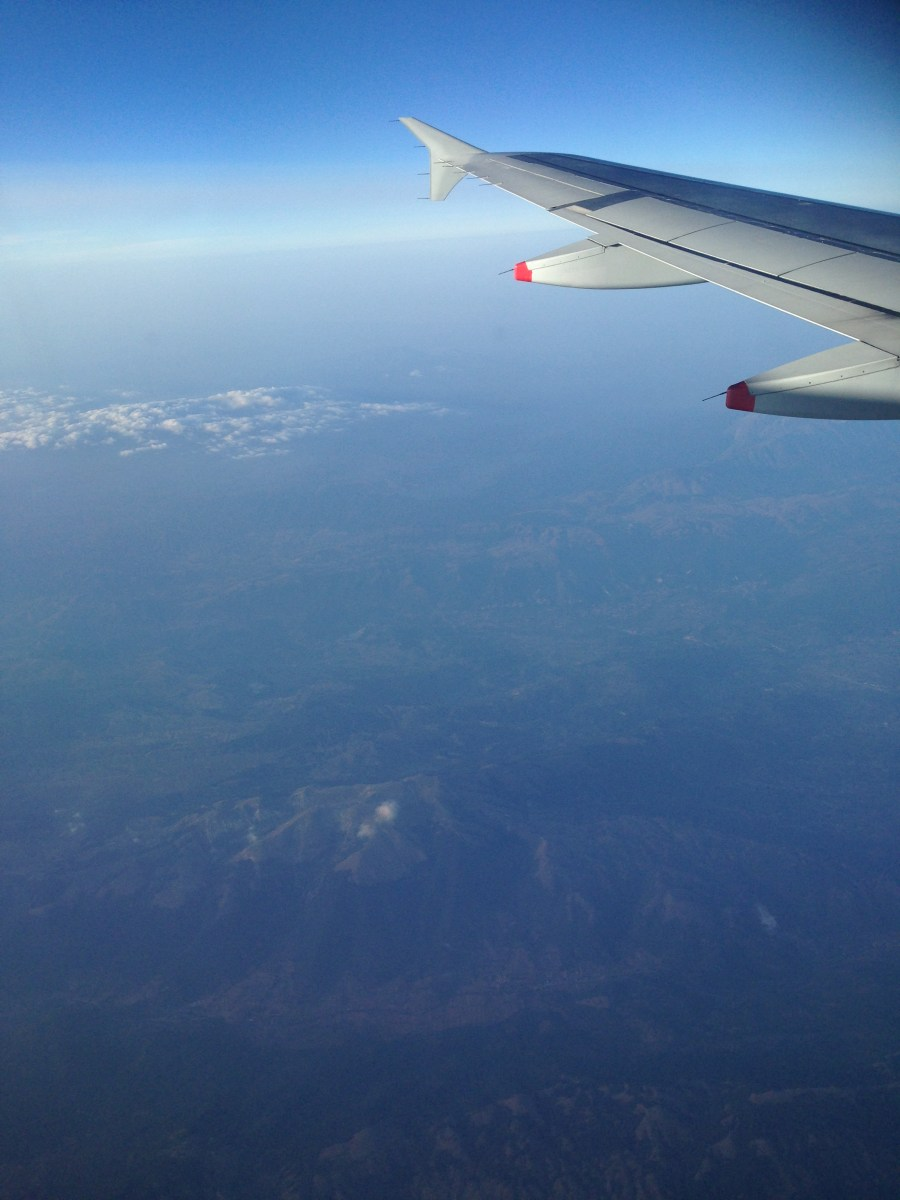 Aeroplane wing and view of mountains of Austria on clear sunny day