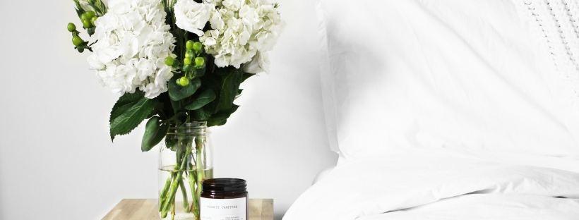 How to edit your life for increased happiness. White flowers in vase on wooden side table next to white covered bed.