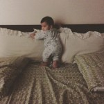 baby standing on a bed