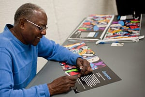 Artist signs first-edition prints of the Compton poster at the Compton Library program.