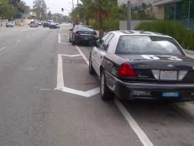 Police car parked on bike lane.