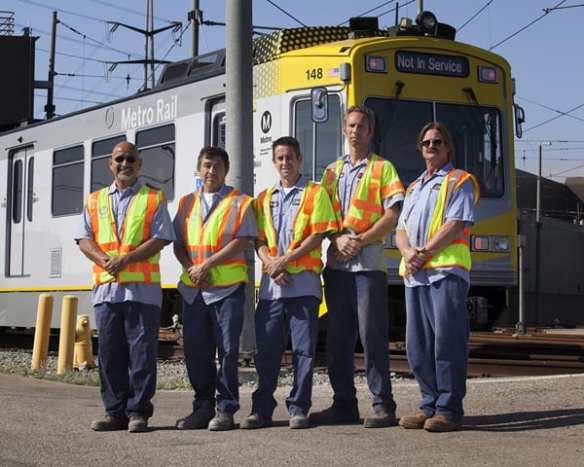 """Detail of the new, bright yellow and white reflective markings and paint scheme rail car styling designed by Metro Creative Services.  A test """"mock up"""" was applied to an older car model by Lee Hetherington (right) in Blue Line Fleet Services and his capable team."""