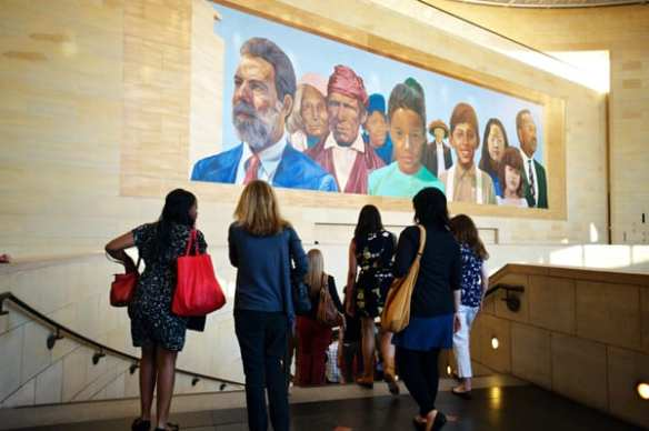 Metro Art tour descending Union Station stairs below the Richard Wyatt mural, City of Dreams, River of History