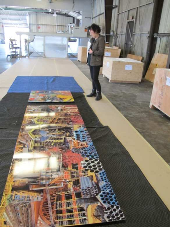 Constance Mallinson inspecting one of her artwork panels after it was delivered by the fabricator to ensure that the colors of her original artwork are accurately reflected in porcelain enamel steel and that the color is consistent among all of the panels.