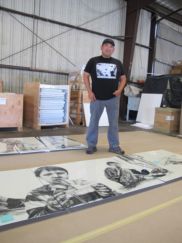 The artist with completed artwork panels.