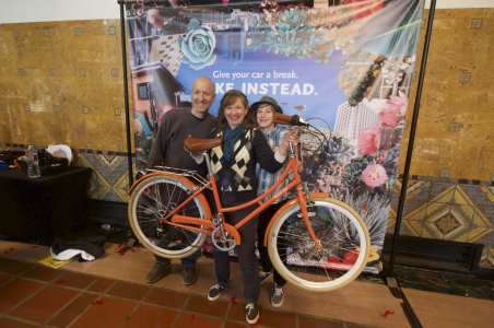 One of the raffle winners shows off her new bike at the photo booth.