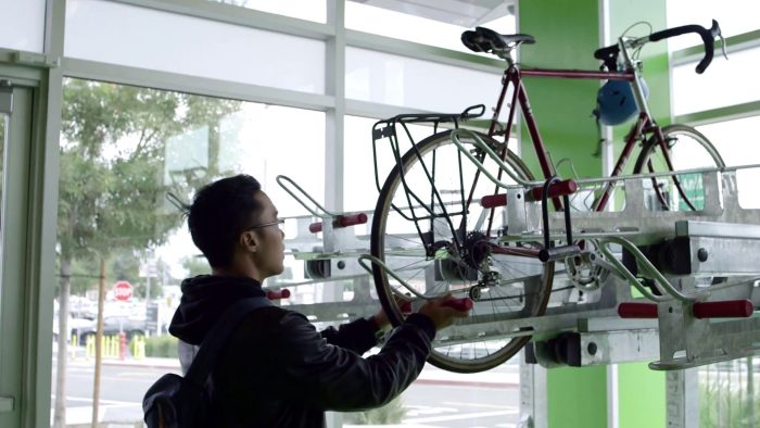 Photo of Akira parking his bike on the double-decker rack.