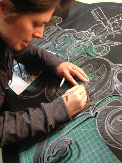 Romero hand-cuts a drawing to create a paper cut piece.