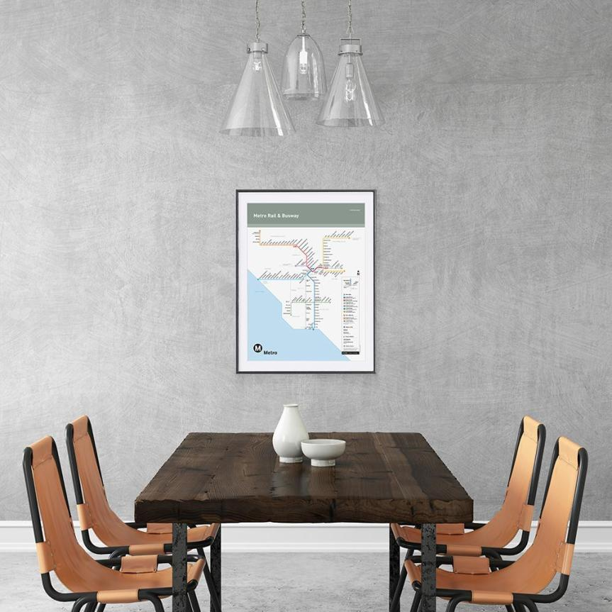 Blank interior wall template with dining table and chairs. Pendant light above. Gray concrete wall, chairs are orange hipster industrial. table made from wood. Go Metro rail map poster on the wall.