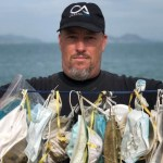 An activist from an oceans conservation group holds up surgical masks that washed up on an island near Hong Kong.